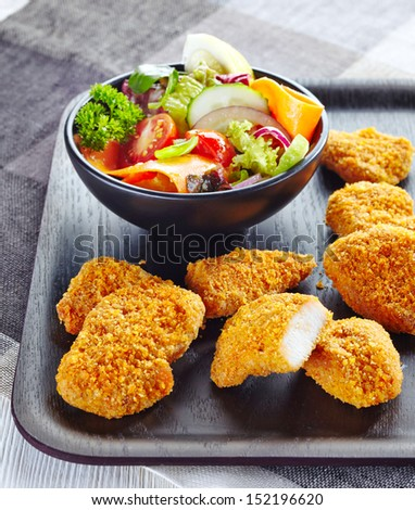 chicken nuggets and fresh vegetable salad - stock photo