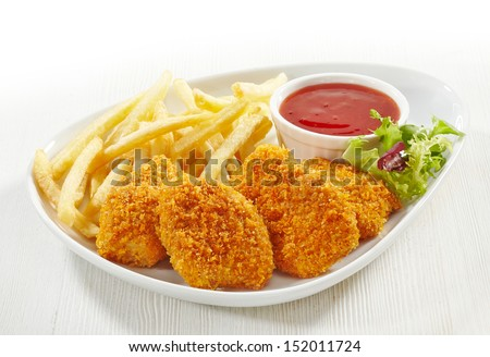 chicken nuggets and fried potatoes on a white plate - stock photo