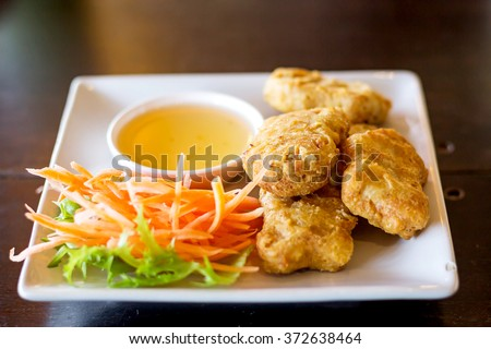 Chicken nuggets and sauce on a wooden background, selective focus - stock photo