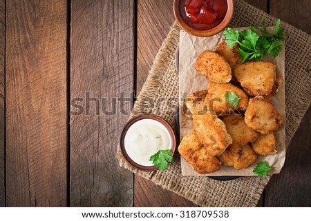 Chicken nuggets and sauce on a wooden background. Top view
