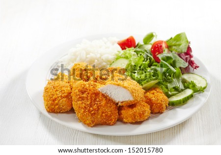 chicken nuggets and vegetable salad on a white plate - stock photo