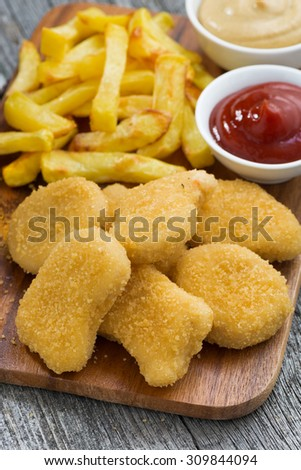 chicken nuggets with french fries and different sauces on wooden board, vertical, top view - stock photo