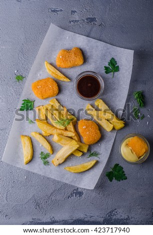 Chicken nuggets with fried potatoes and sauces on stone background. Selective focus. Vertical top view - stock photo