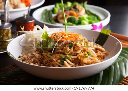 Chicken pad Thai with a variety of other fine Thai food dishes.  Shallow depth of field. - stock photo