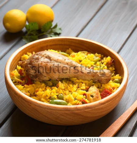 Chicken paella, a traditional Valencian (Spanish) rice dish made of rice, chicken, peas and capsicum in wooden bowl, photographed with natural light (Selective Focus, Focus on the chicken thigh) - stock photo