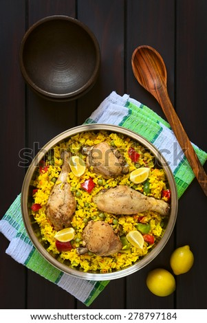 Chicken paella, a traditional Valencian (Spanish) rice dish made of rice, chicken, peas and capsicum and served with lemon in cooking pot, photographed overhead on dark wood with natural light - stock photo