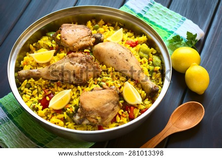 Chicken paella, a traditional Valencian (Spanish) rice dish made of rice, chicken, peas, capsicum, lemon, photographed on dark wood with natural light (Selective Focus, Focus on middle of the dish) - stock photo