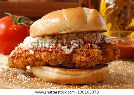 Chicken parmesan sandwich (seasoned and fried chicken breast with tomato basil marinara sauce and mozzarella on a grilled bun) with ingredients and cooking oil in background.  Macro with shallow dof. - stock photo