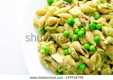chicken pesto pasta with chicken, basil and parmesan cheese and sweet peas - stock photo