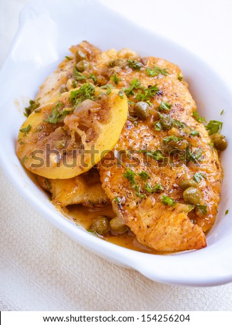 Chicken Piccata dish with meat sliced, coated with sauce and served in a sauce.  - stock photo