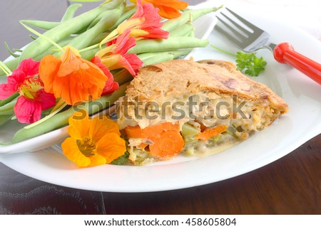 Chicken pot pie baked with leftover roast chicken, your favorite vegetables and store bought frozen crust served with home grown green beans and spicy edible annual flowers - stock photo