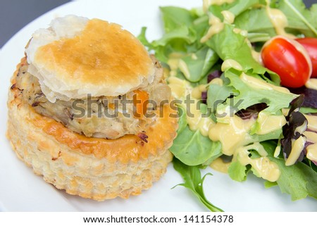 Chicken Pot Pie with Leafy Green Vegetables Tomatoes and Salad Dressing Closeup