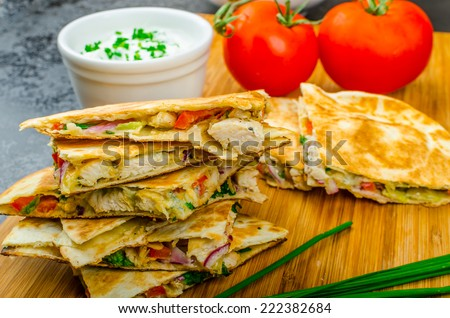 Chicken quesadilla with tomato, red onions, parsley and red pepper, fresh salad and creame sour-chive dip - stock photo