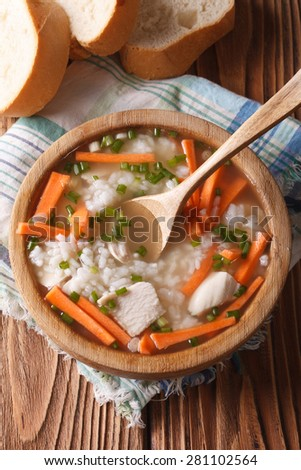 Chicken rice soup close up in a wooden bowl. vertical top view