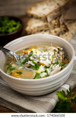 Chicken rice soup with vegetables in bowl and bread on rustic table - stock photo