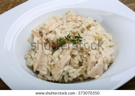 Chicken risotto with cheese and thyme branch