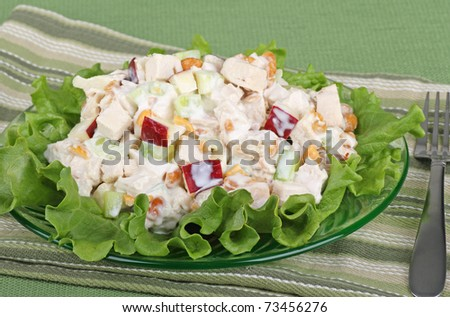 Chicken salad with apple pieces on top of a lettuce leaf
