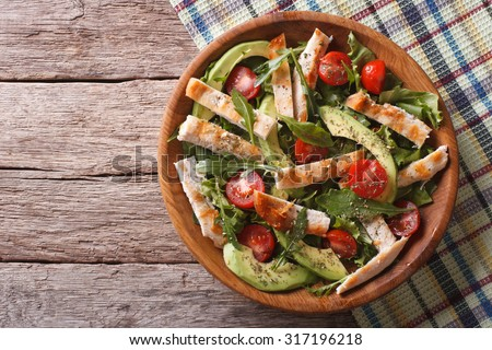 Chicken salad with avocado, arugula and cherry tomatoes in a wooden plate. horizontal view from above