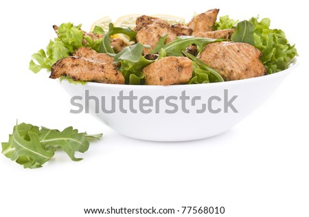 Chicken salad with dropped leaves over white background - stock photo