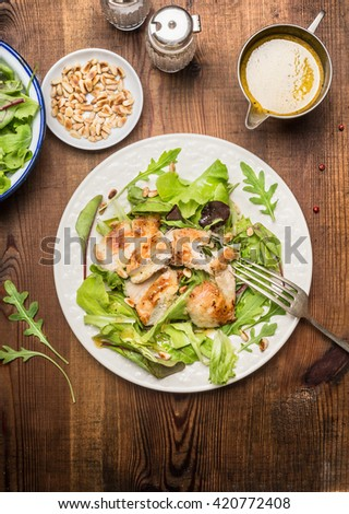 Chicken salad with green salad leaves, pine nuts and olive oil dressing. Healthy diet salad on rustic wooden background, top view. Country chicken salad. - stock photo