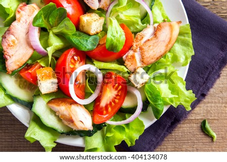 Chicken salad with leaf vegetables and tomatoes over rustic wooden background