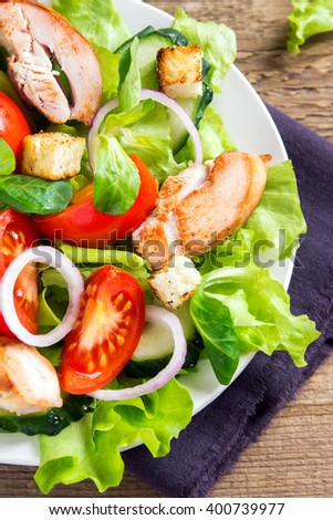Chicken salad with leaf vegetables, tomatoes and croutons close up