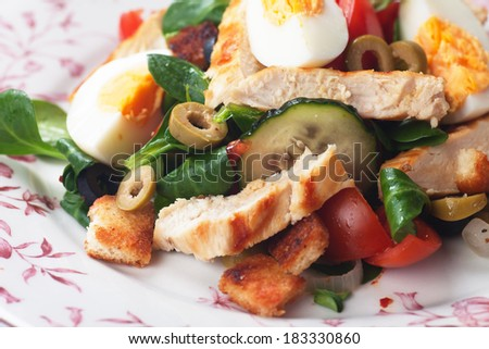 Chicken salad with olives, tomato, croutons, and cornsalad