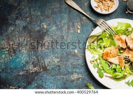 Chicken salad  with pine nuts on rustic background, top view, place for text. Healthy lifestyle and diet food concept. - stock photo