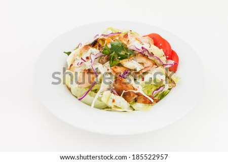 Chicken salad with tomatoes, arugula in the white bowl