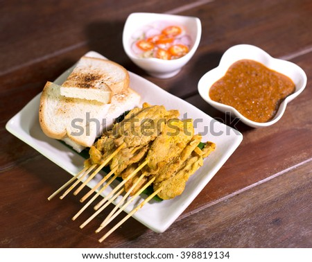 Chicken Satay and toast served with peanut sauce and vegetable salad sauce / Selective focus - stock photo