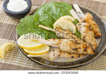Chicken Satay - Char-grilled mini chicken fillet skewers served with lemon and aioli dip. - stock photo