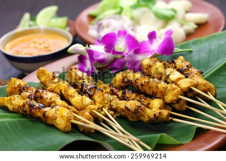 chicken satay, sate ayam and lontong with peanut sauce, indonesian skewer food - stock photo