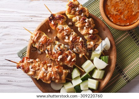 Chicken satay with a delicious peanut sauce and fresh salad on the plate closeup. horizontal top view - stock photo