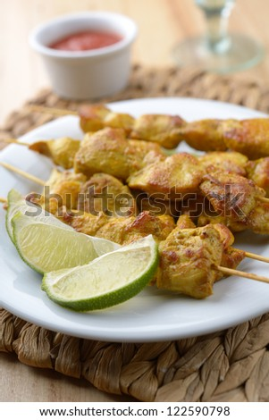 Chicken satay with slices of lime and sauce