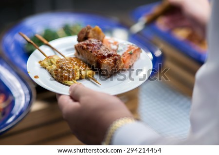 Chicken satek , grilled beef , grilled salmon and grilled chiken on the dish of people in the line of catering buffet food - stock photo
