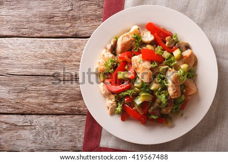 Chicken saute with mushrooms and vegetables close-up on a plate. Horizontal view from above