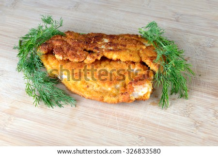 chicken schnitzel and dill on a wooden tray - stock photo