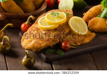 Chicken schnitzel and homemade potato croquettes with cheese and chilli - stock photo