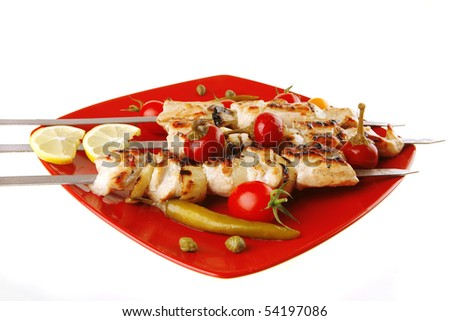 chicken shish kebab on red platter with vegetables - stock photo