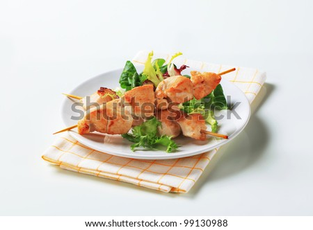 Chicken skewers and salad greens  - stock photo