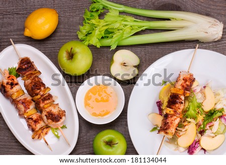 Chicken skewers with apple and salad in a white plate on a wooden table with green apples, honey, lemon and celery - stock photo