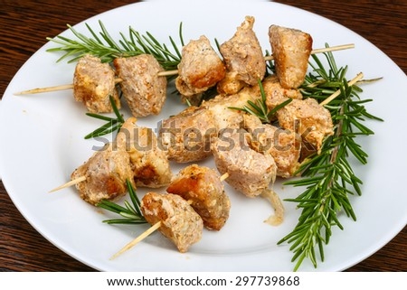 Chicken skewers with rosemary branch on the white plate - stock photo