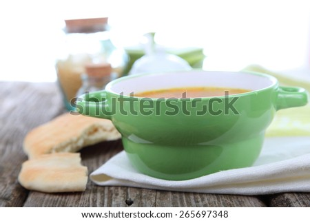 Chicken soup in green bowl on a wooden table - stock photo