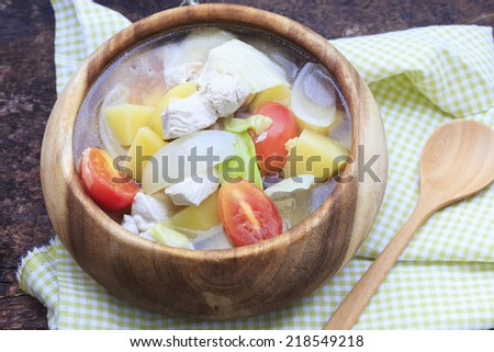 Chicken soup in wooden bowl