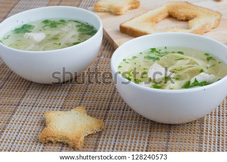 Chicken soup served with noodles, parsley and toasts