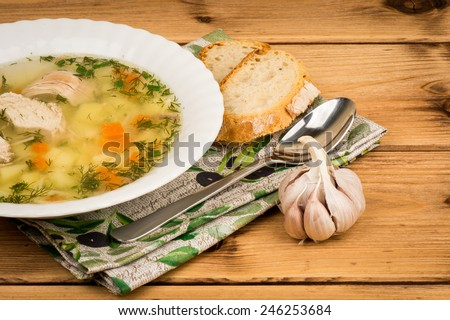 Chicken soup with a bread and garlic on the wooden background. - stock photo