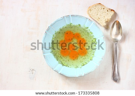 chicken soup with carrots over white wooden textured background - stock photo