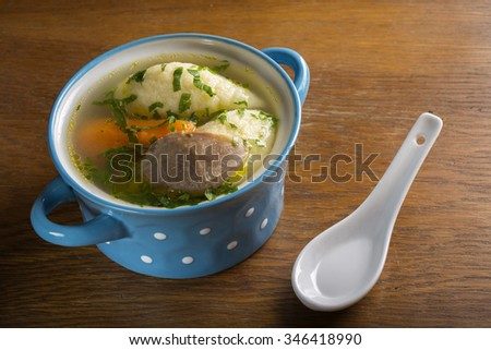 Chicken soup with dumplings in blue bowl on wooden table - stock photo