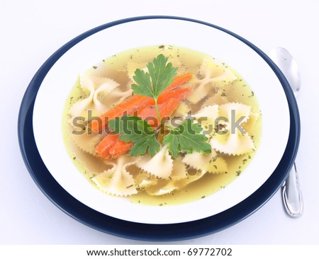 Chicken soup with farfalle pasta and carrots decorated with parsley on a plate with a spoon - stock photo
