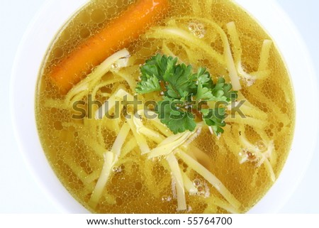 Chicken soup with macaroni and carrots decorated with parsley - stock photo